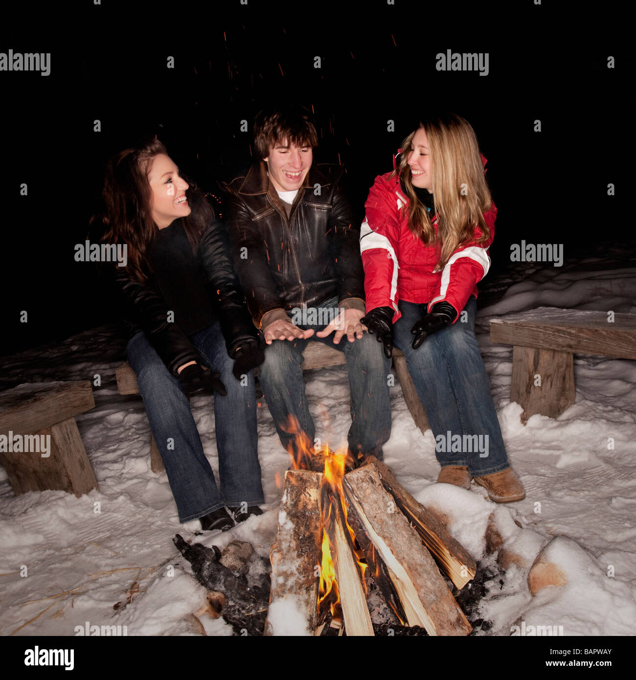 Teenagers sitting by a fire - Stock Image