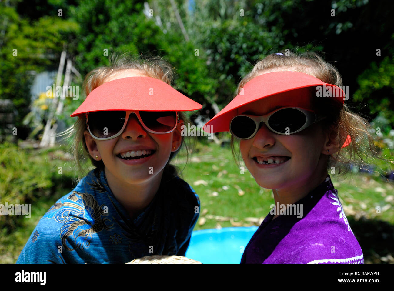 Two sisters (10 years old and 7 years old) wearing fashionable sunglasses and sun visors - Stock Image