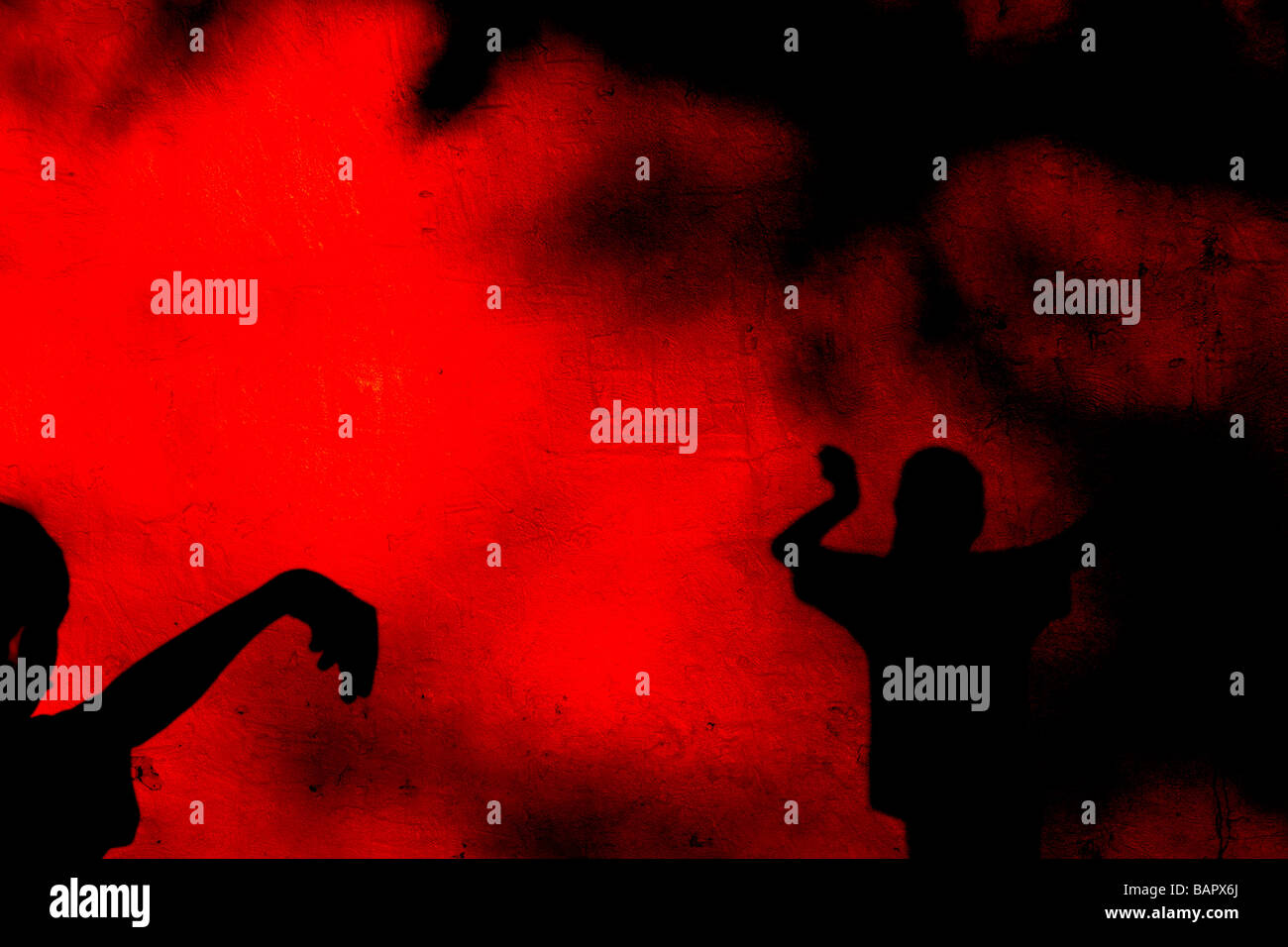 Children casting shadows on a rough red wall - Stock Image