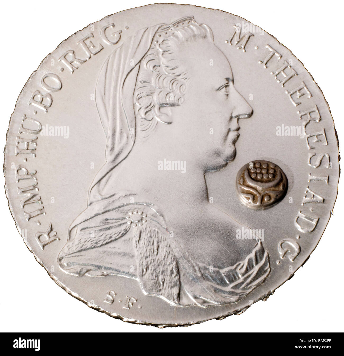 Maria Theresa Austrian Silver Thaler and tiny Indian silver 1/16th Rupee. Contrasting coin sizes - Stock Image