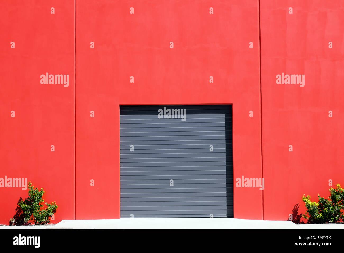 Grey roller garage door in red brick wall - Stock Image