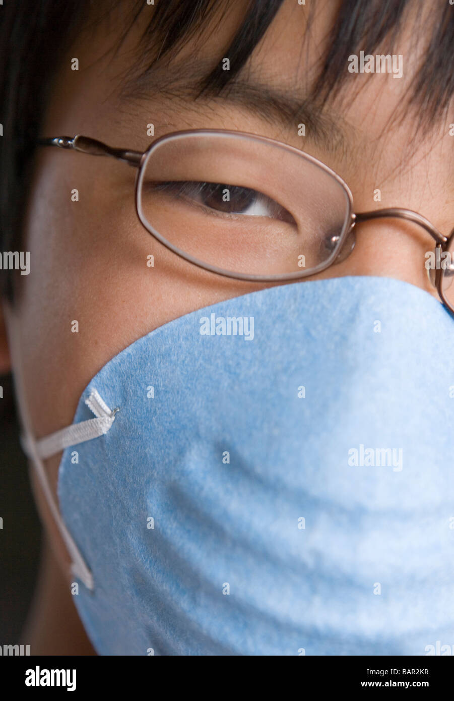closeup of japanese twelve year old boy wearing a mask - Stock Image