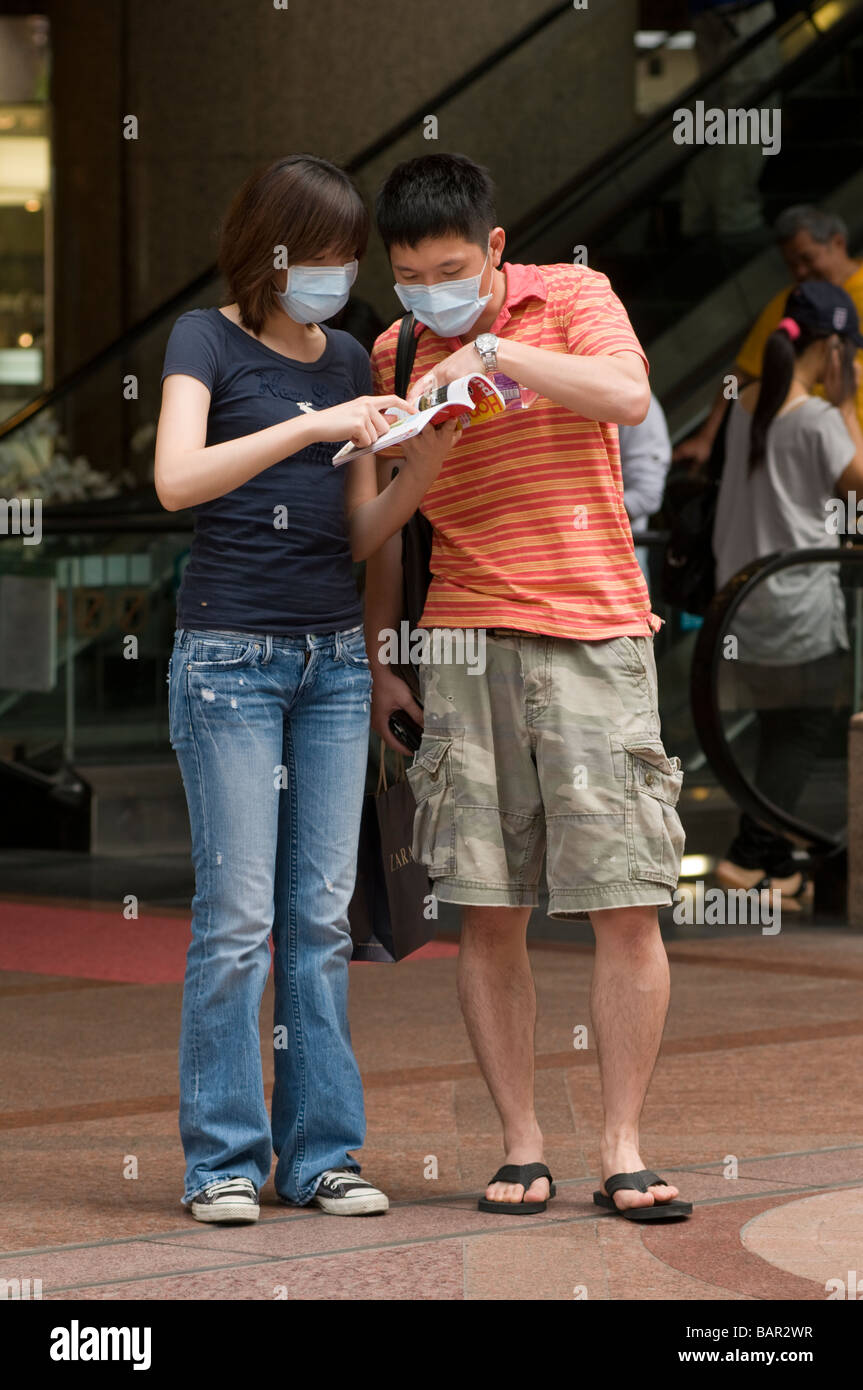 Tourists wear surgical masks as protection against swine flu Hong Kong May 2009 - Stock Image