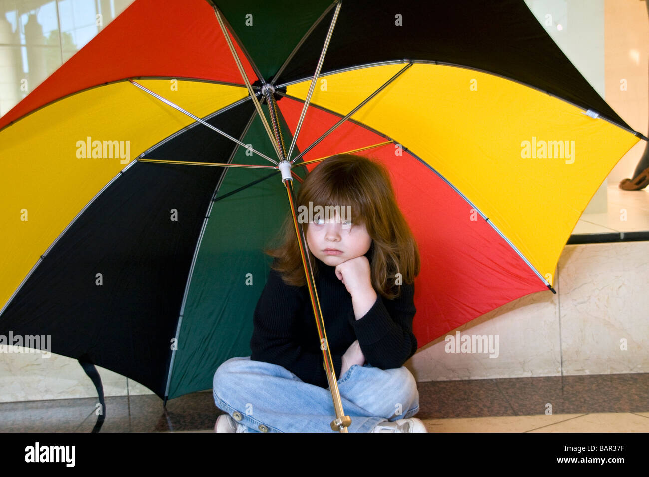 Small girl bored sitting on the ground under a large umbrella inside the Overgate shopping mall in Dundee UK - Stock Image