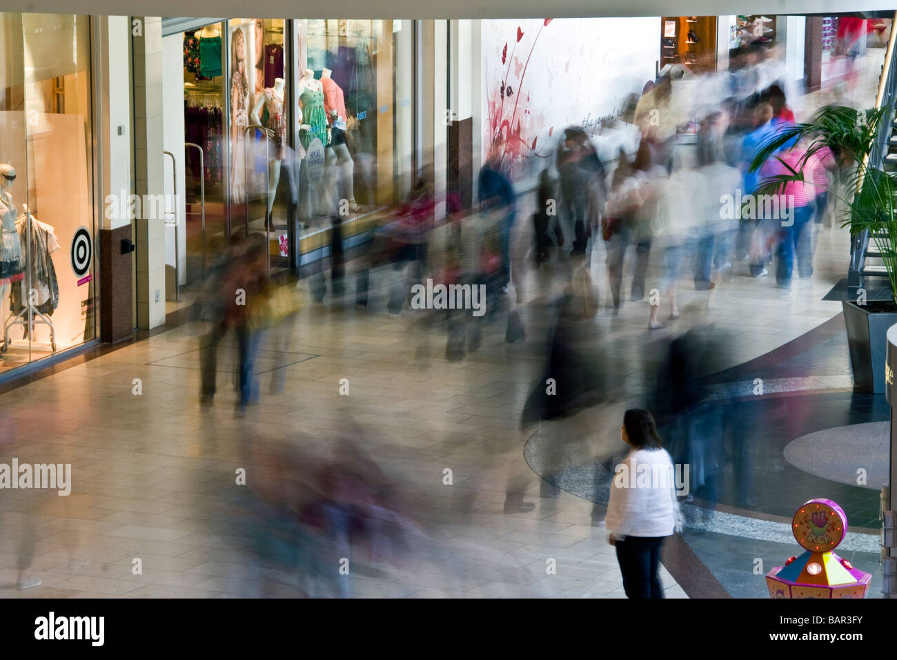 Lonely shopper stands out from everyone else during rear sync flash photography in the Overgate shopping mall in Stock Photo