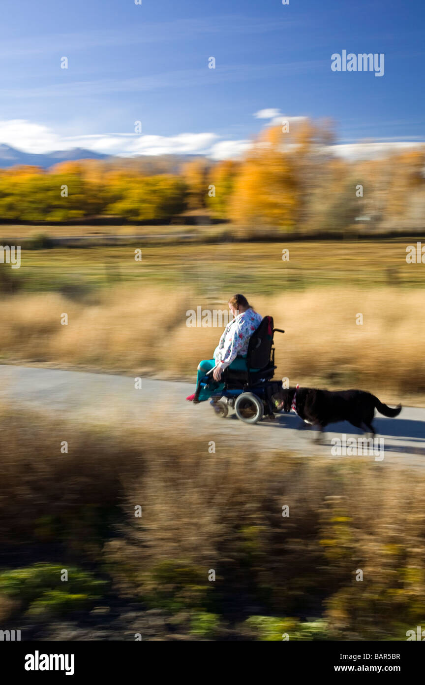 Woman uses her electric wheelchair to navigate the walking path in the small mountain town of Salida Colorado USA - Stock Image