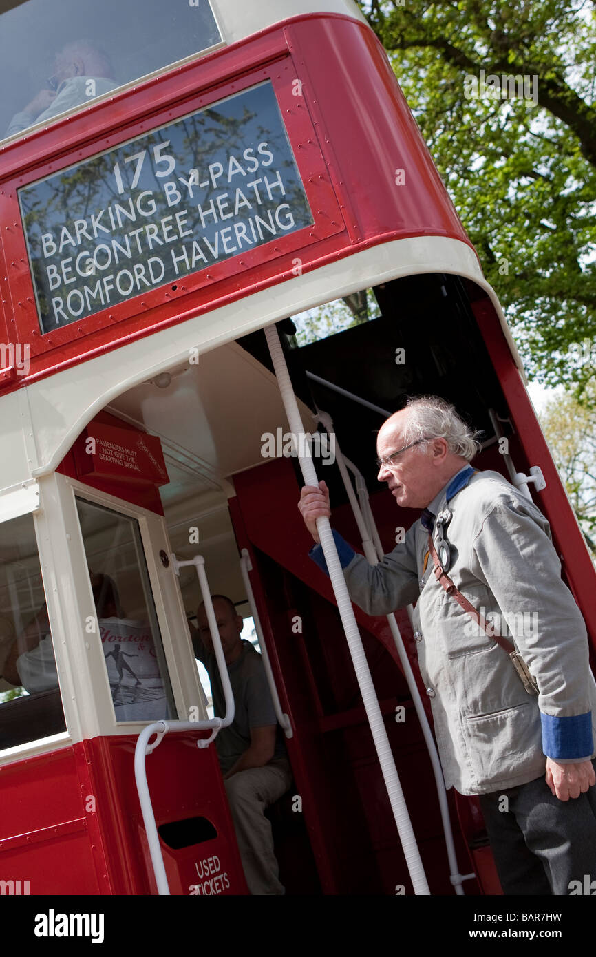 Man dressed as bus conductor on open platform of traditional style  London double decker bus, vintage commercial - Stock Image