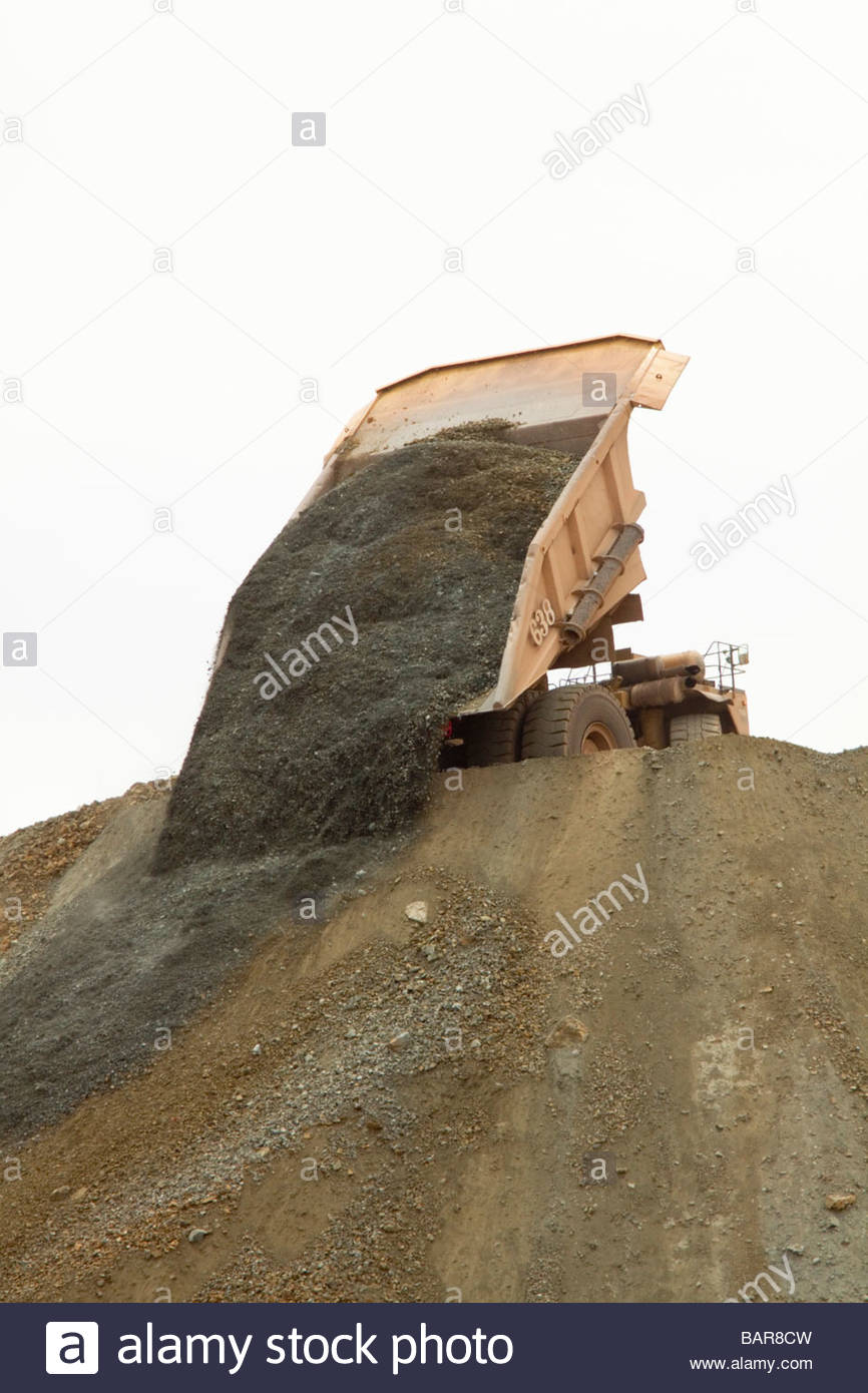 Mine haul truck dumping waste over dump - Stock Image