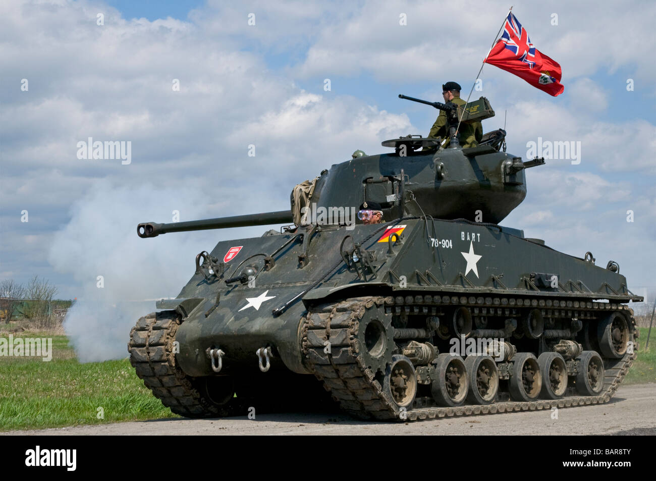 A fully restored IV Sherman tank flying the World War Two Canadian flag. Its main gun has just been fired. - Stock Image
