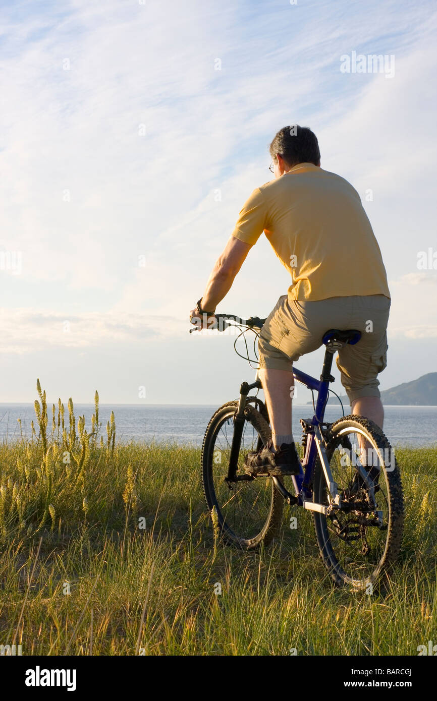 Man riding his bicycyle at the sea in the morning - Stock Image
