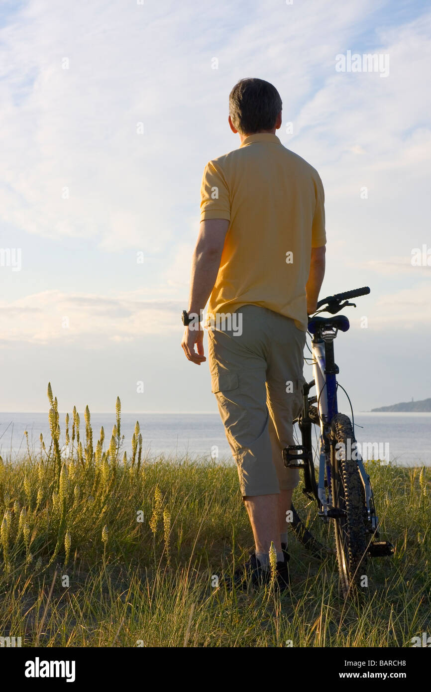 Man standing by his cycle at the sea - Stock Image