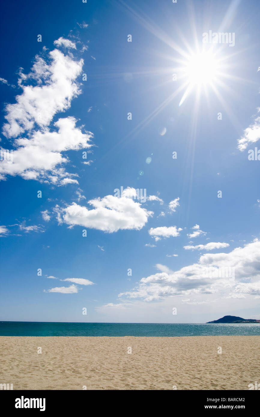 Sun shining on the beach with blue sky and clouds - Stock Image
