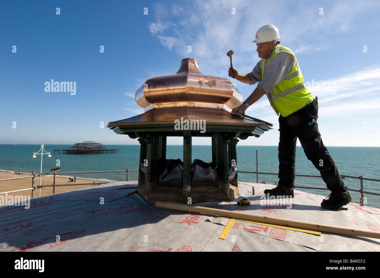 A coppersmith restores the cupola of Brighton Bandstand on the seafront - Stock Image