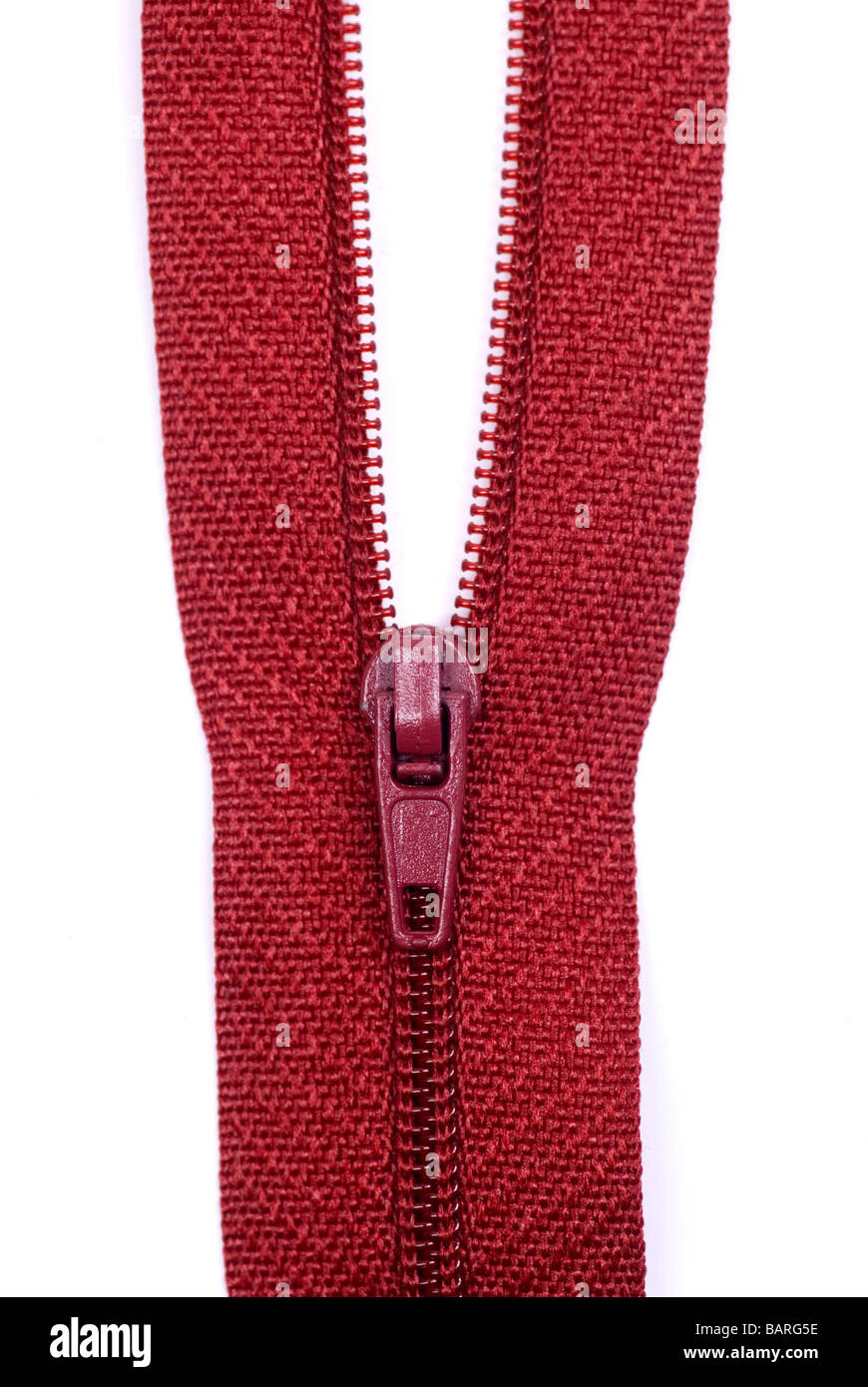 Close up of a red zipper against a white background - Stock Image