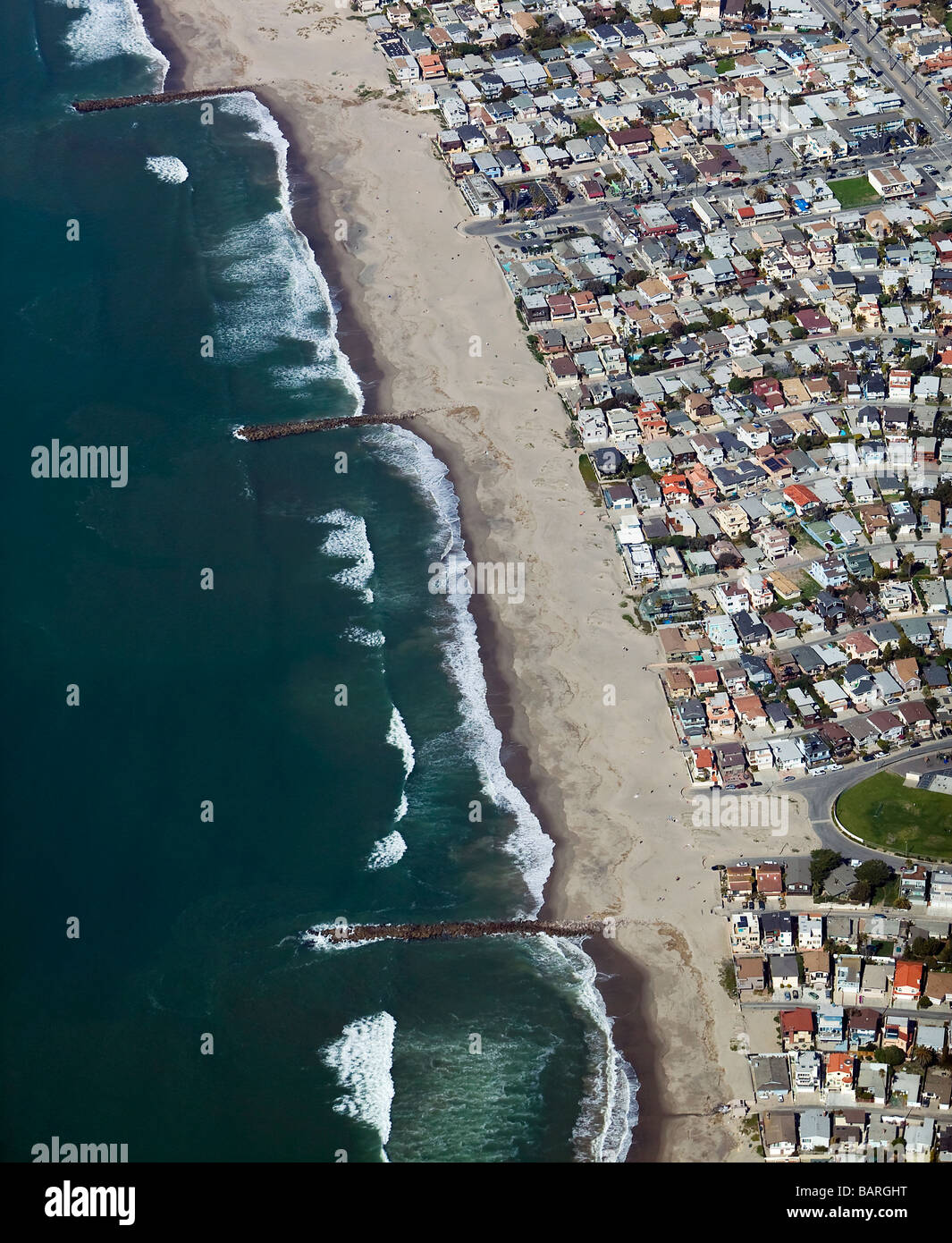 aerial view above breakwaters controlling coastal erosion residential development southern California - Stock Image