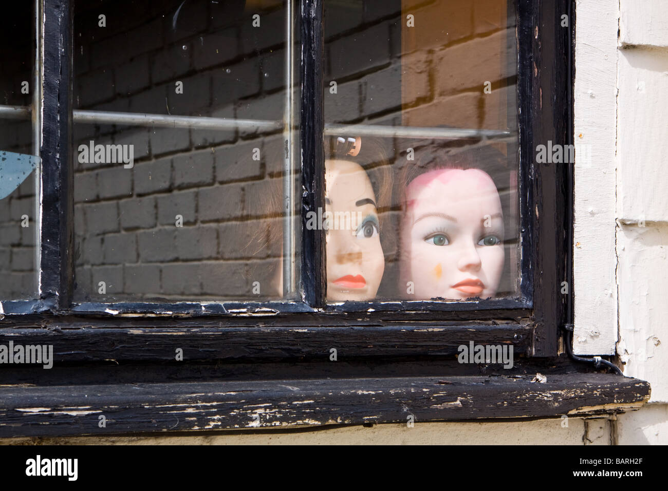 Mannequin Heads Looking Through a Window - Stock Image