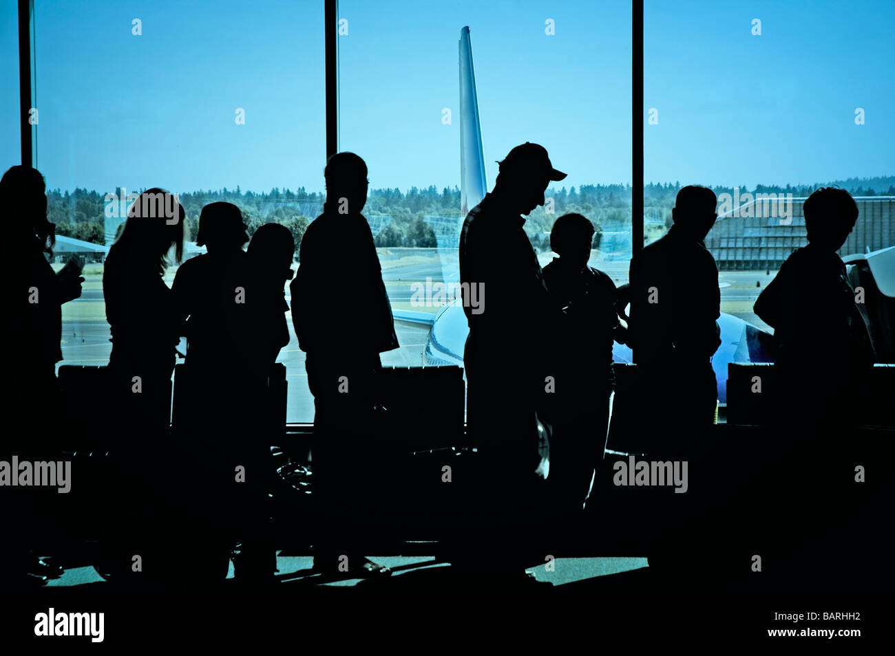 Travelers standing in line at the airport waiting to board an airplane Stock Photo