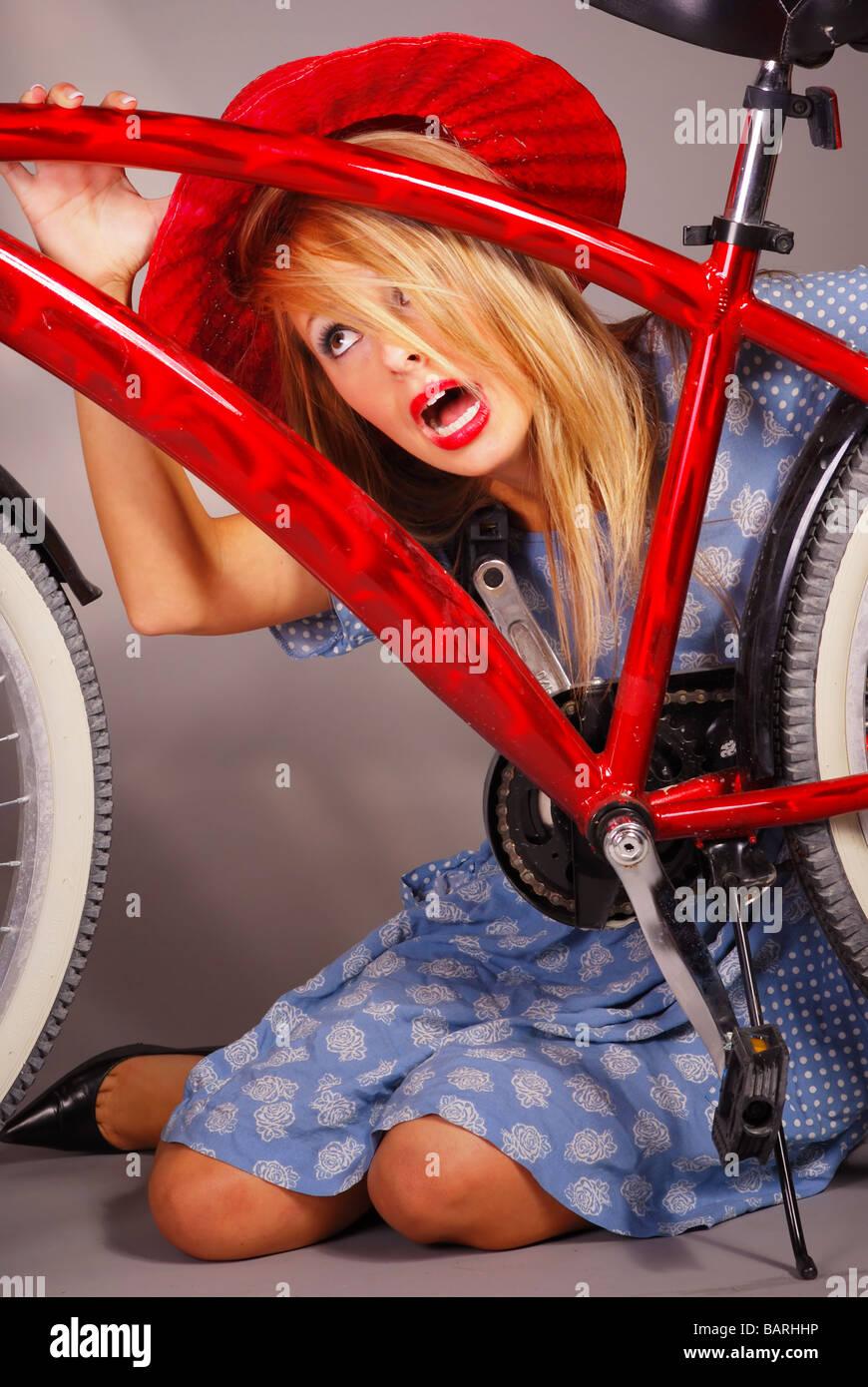 Blonde teenage girl wearing hat standing behind red bicycle Stock Photo