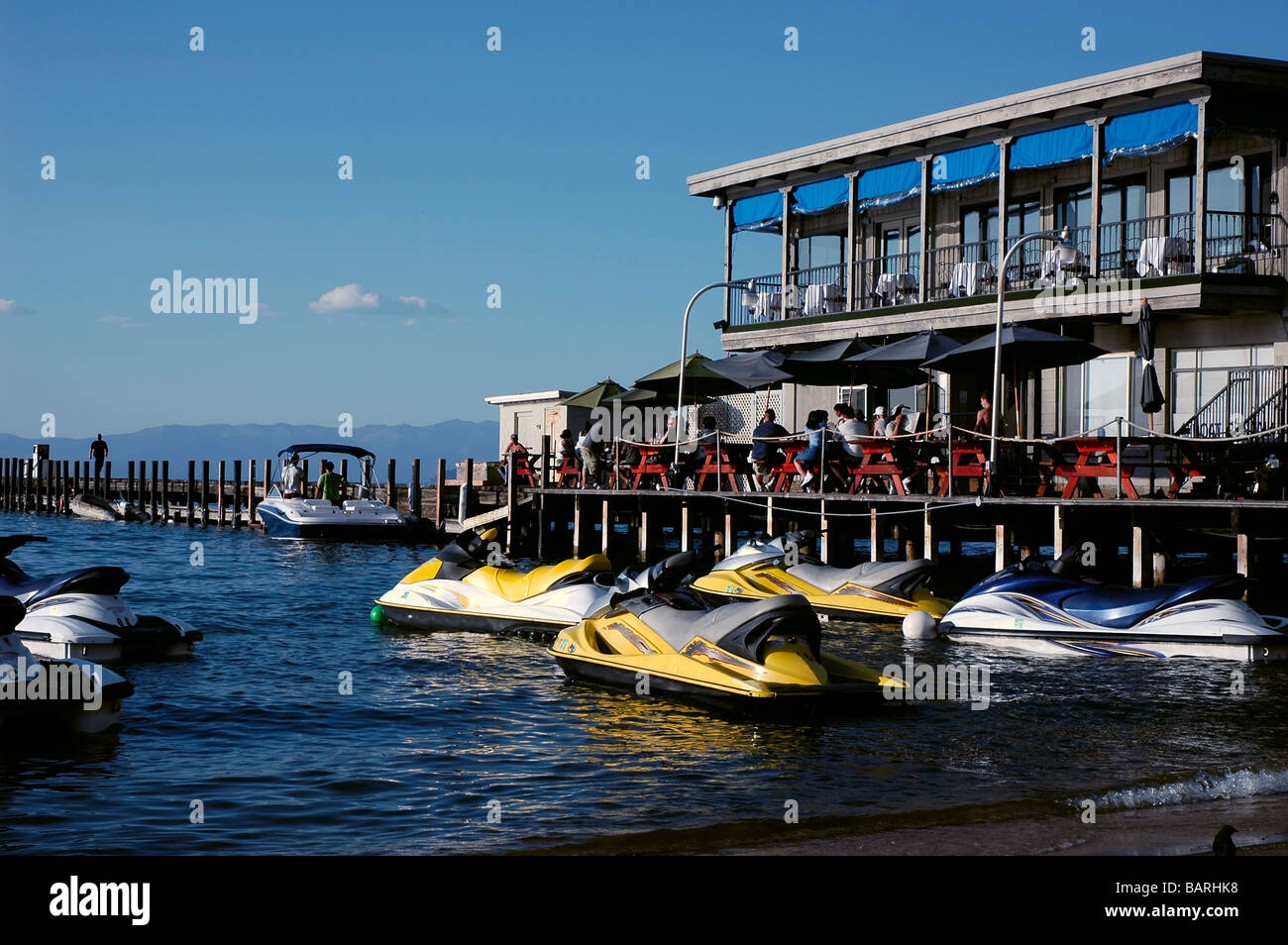 Diners eating at an outdoor restaurant near a jet ski rental business on a lake Stock Photo