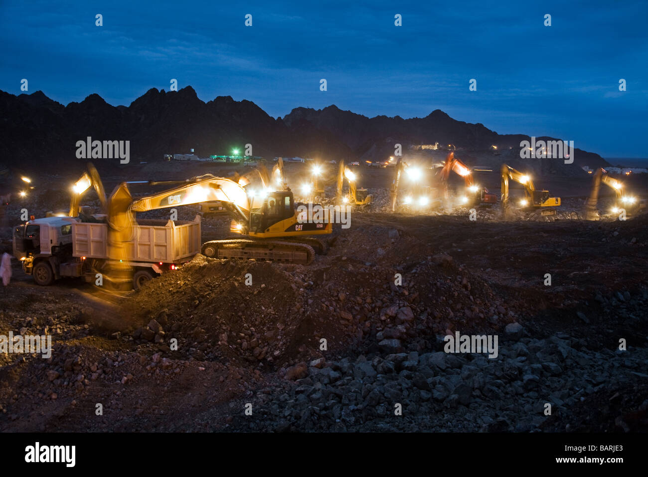 Construction site at night with lots of diggers flattening an area near Mutrah for new buildings nächtliche - Stock Image