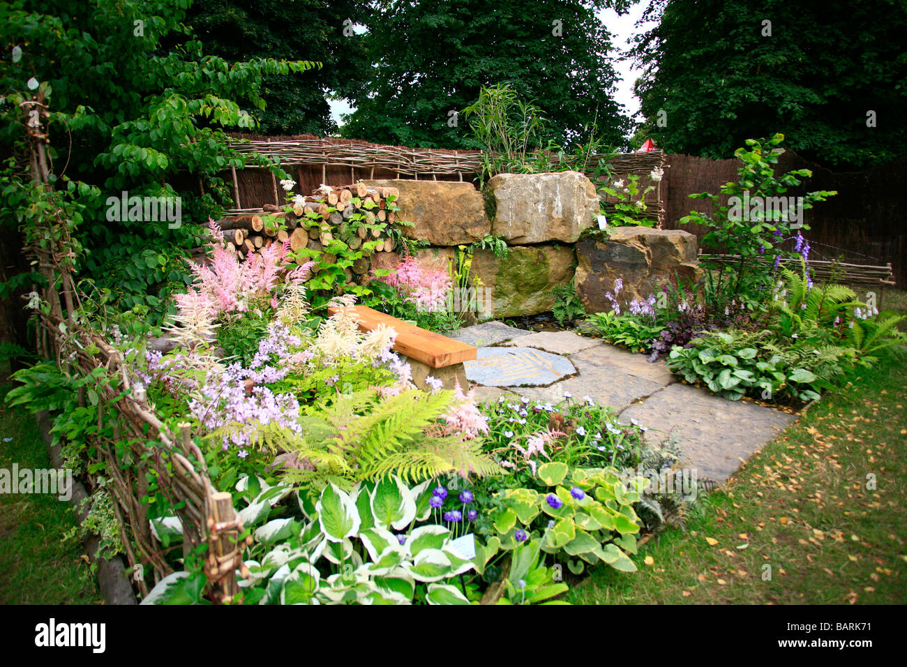 Show garden with rock wall and paved area, surounded by borders planted with perennials - Stock Image