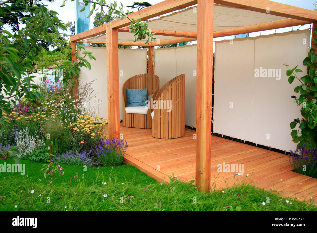 Pergola with sailcloth sides and roof over decked area with tub chairs - Stock Image