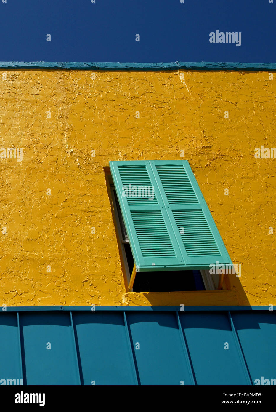 open tourquoise colored window on a bright yellow and blue wall at the beach with dark blue sky - Stock Image