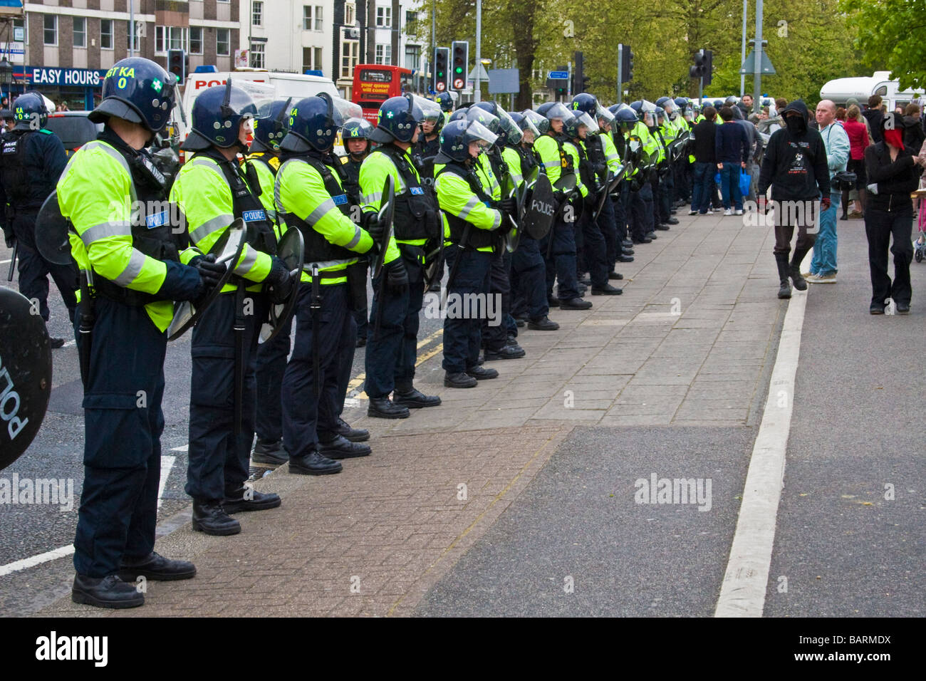 Riot police line the road observing protests during may day protests in Brighton, Sussex, UK JPH0192 - Stock Image