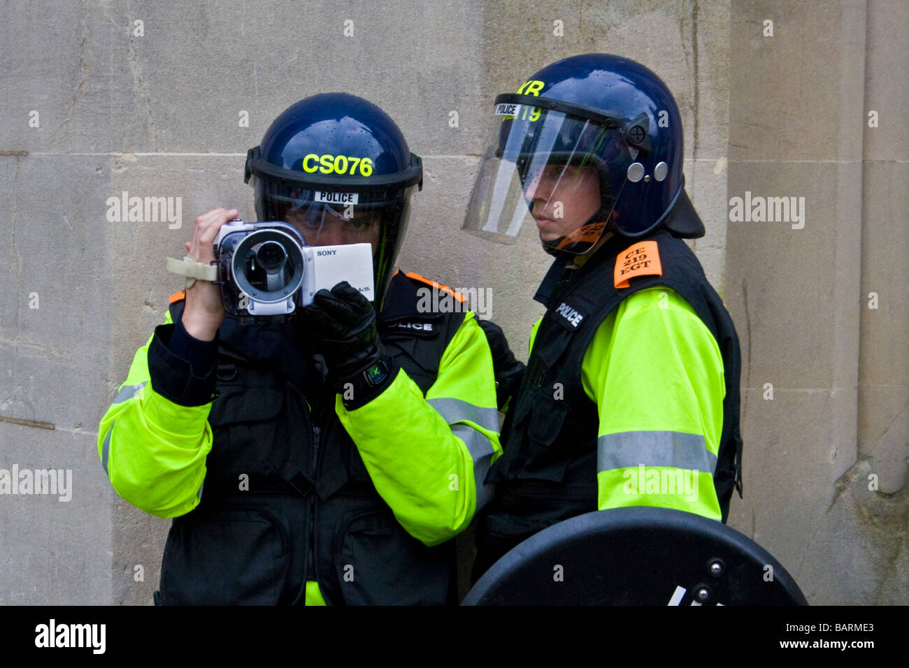 Riot police filming the crowd and events during may day protests in Brighton, Sussex, UK JPH0193 - Stock Image