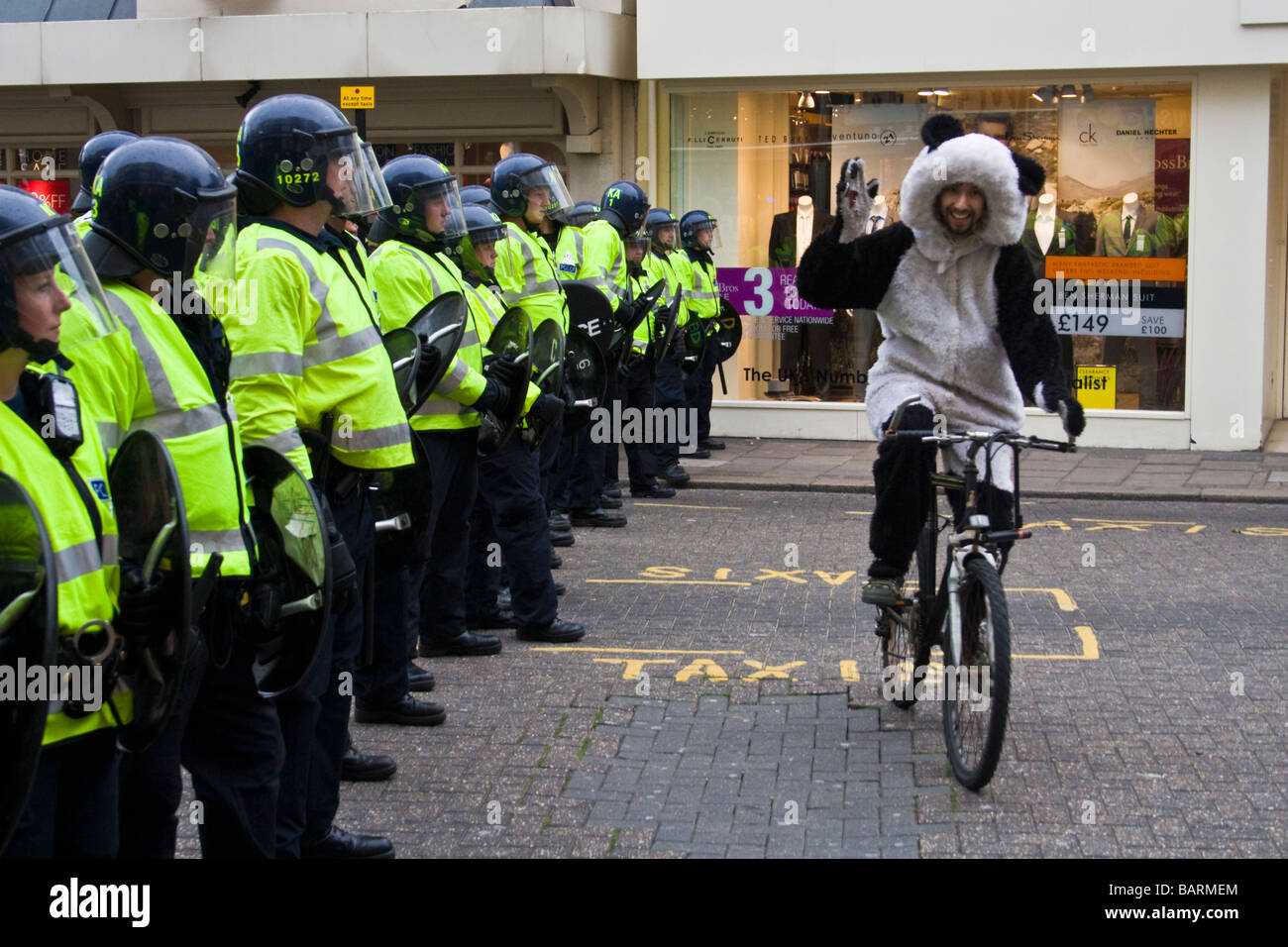Man dressed in panda suit cycles in front of a line of riot police during may day protests in Brighton, Sussex, - Stock Image