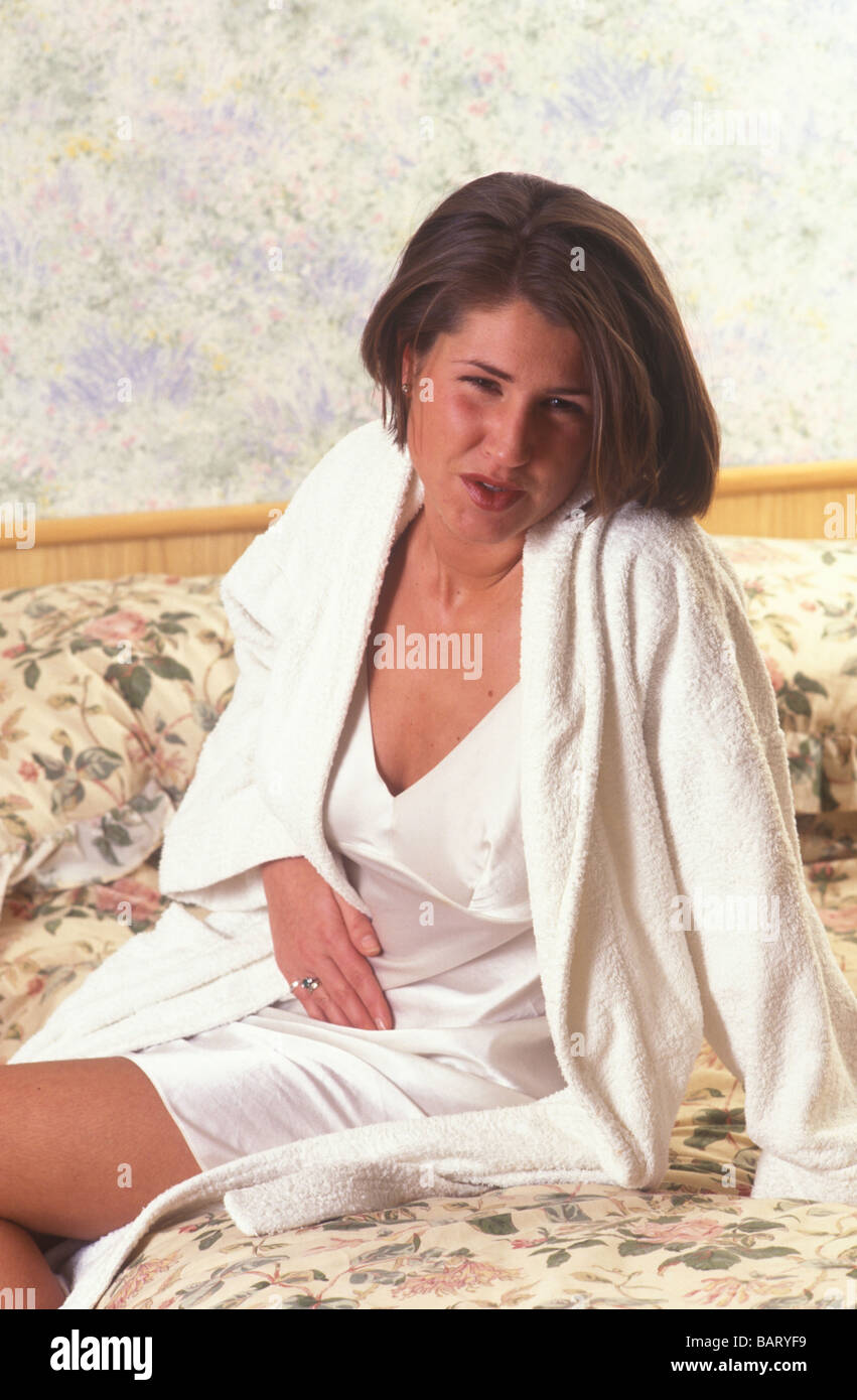 woman in dressing gown and nightdress in pain with tummy ache Stock ...