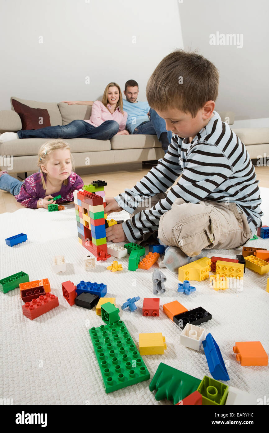 Family relaxing at home, children playing with building bricks Stock Photo