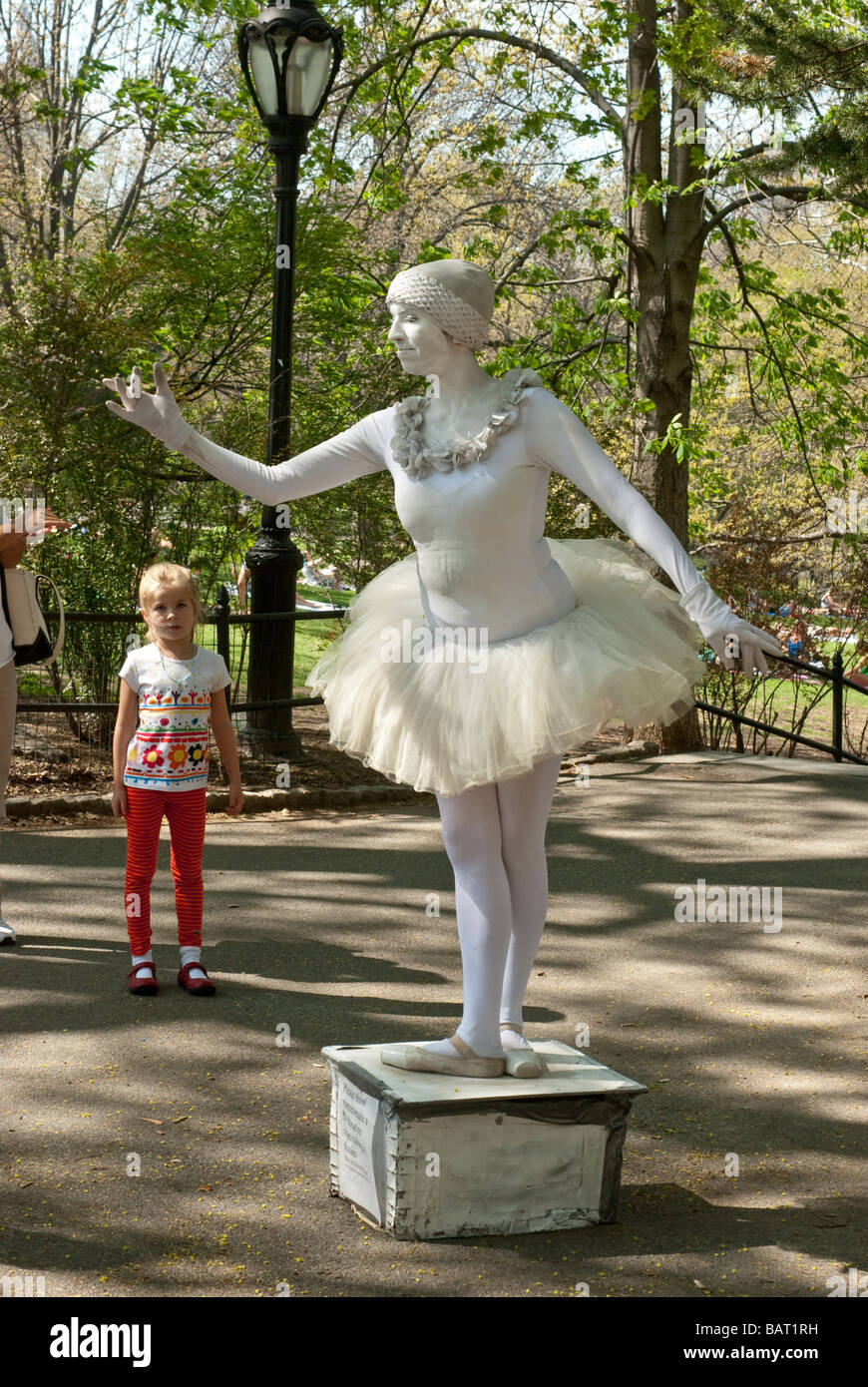 a busker ballerina mimes a statue, watched by a serious little girl, in Central Park, New York City - Stock Image