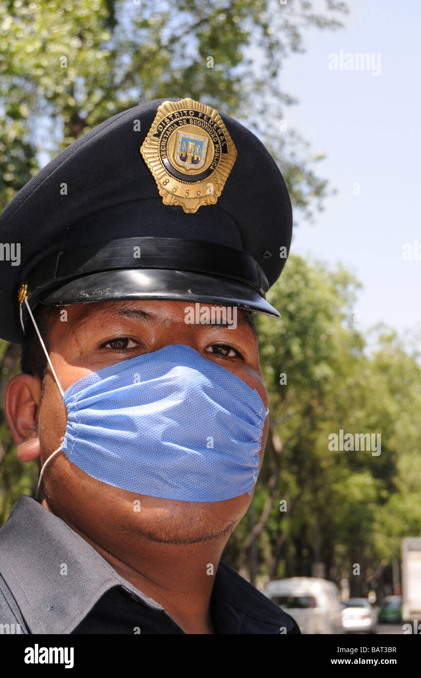 Closeup of a Mexican police officer who protects himself with a face mask against influenza - Stock Image