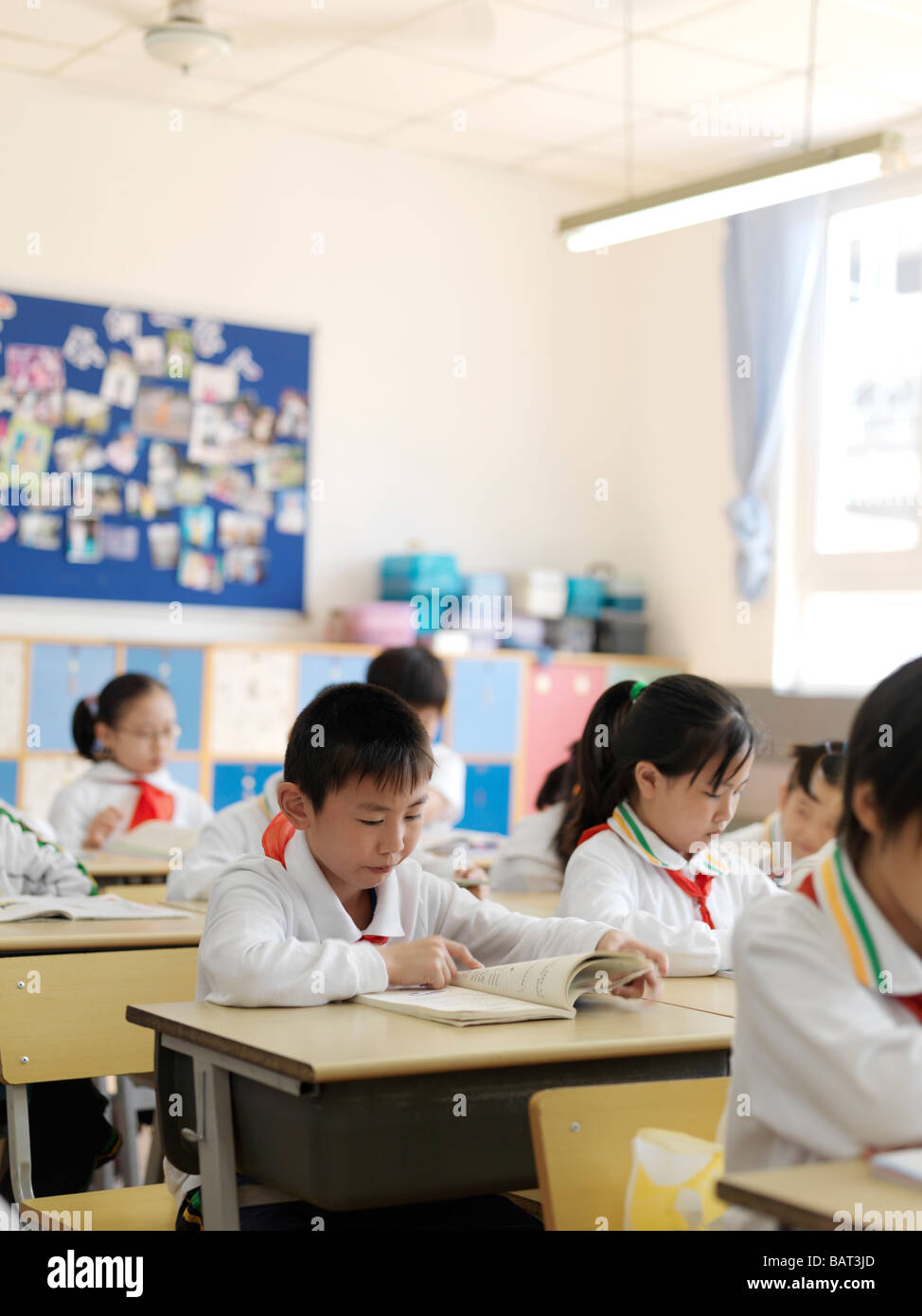 A classroom of young students reading a lesson from their textbook - Stock Image