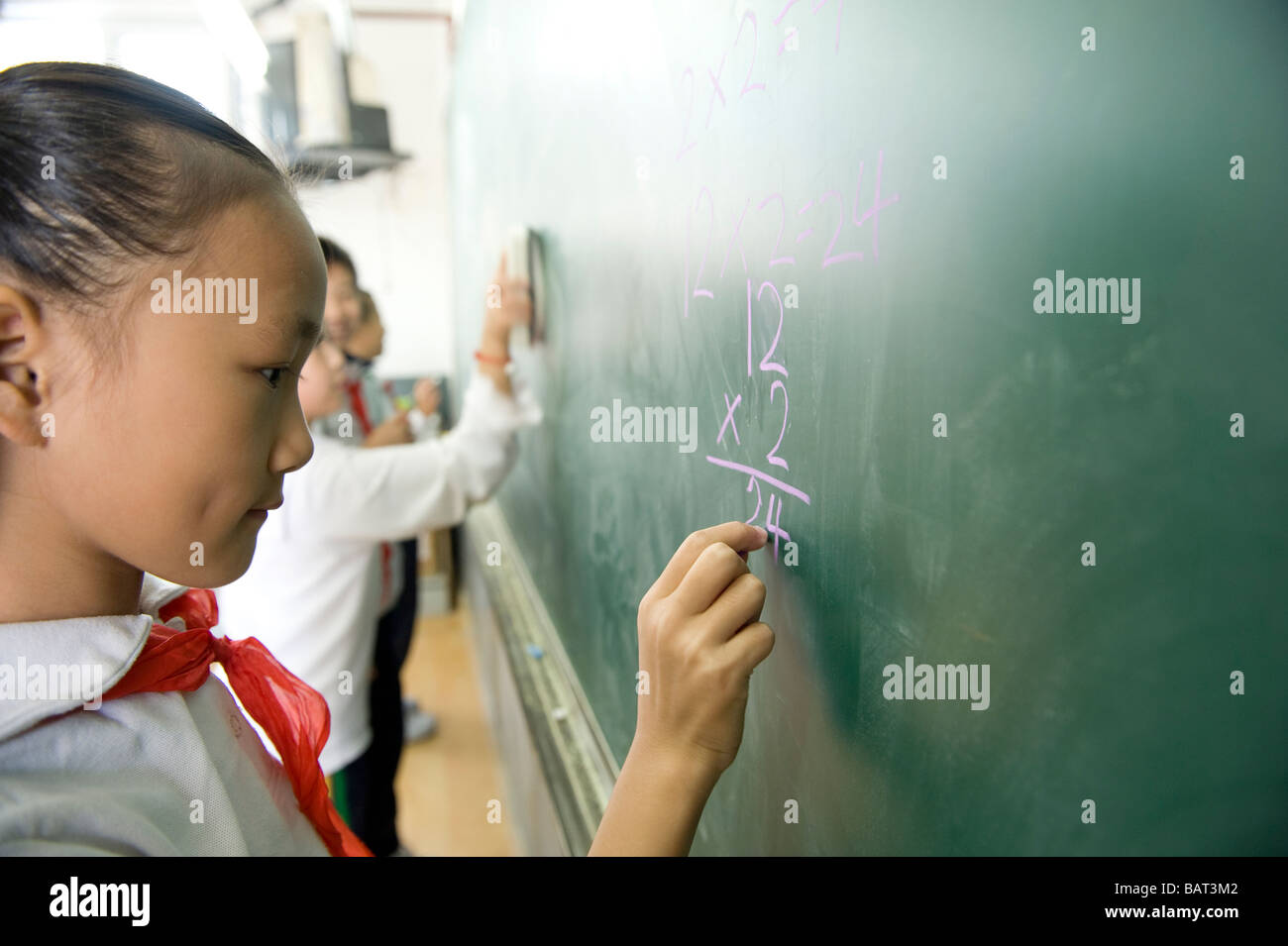 Young student practicing math on a chalkboard. - Stock Image