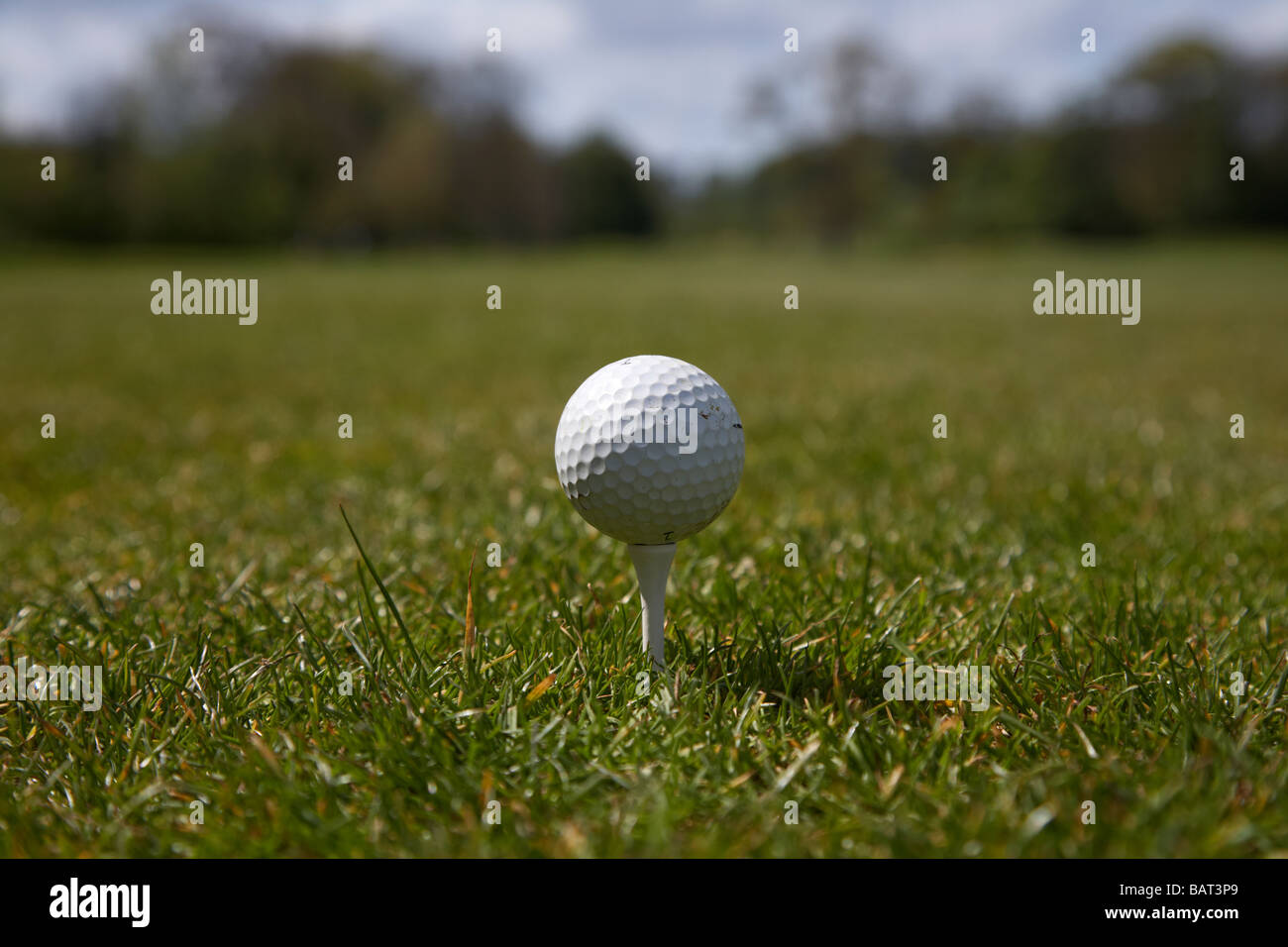 used golf ball sitting on the tee at the start of a golf course county armagh northern ireland - Stock Image