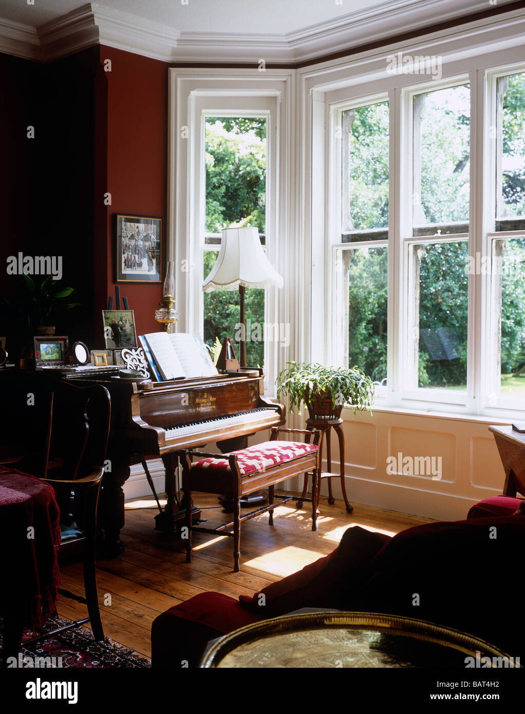 Steinway Baby Grand Piano infront of a bay window in a traditional