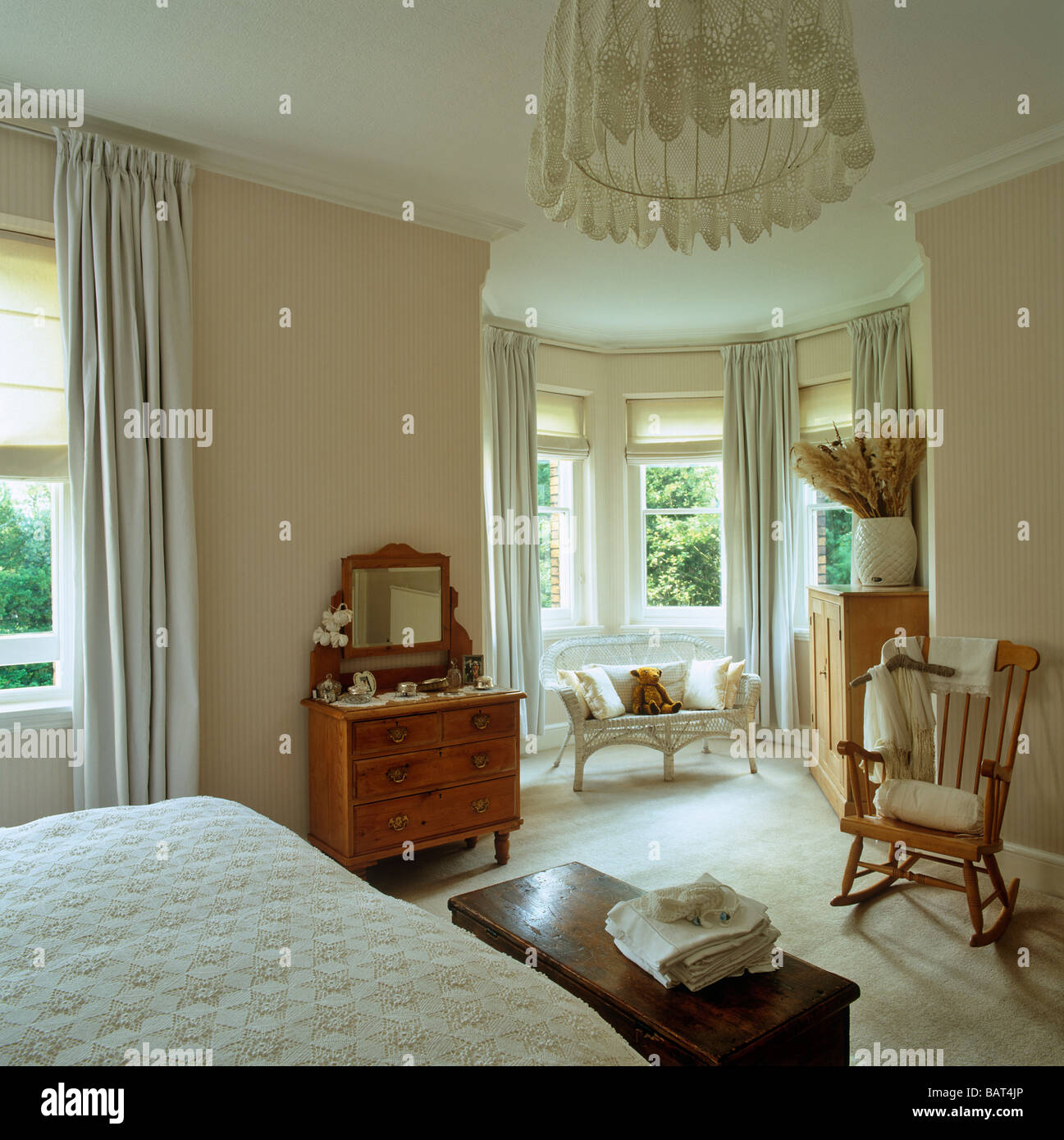 Pale bedroom with pine furniture and bay window - Stock Image