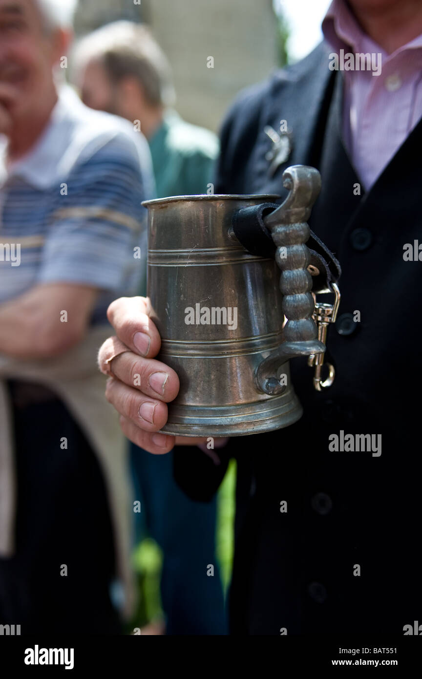A hand holding a pewter tankard. - Stock Image