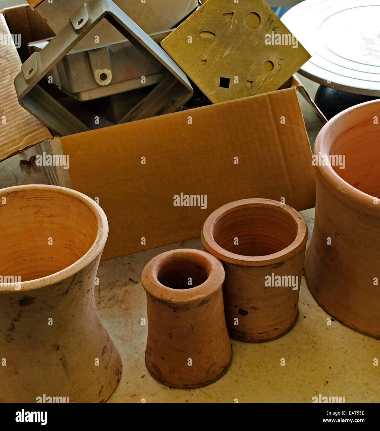 pottery awaiting firing bisque raw turned, with tools in background wheel, box - Stock Image