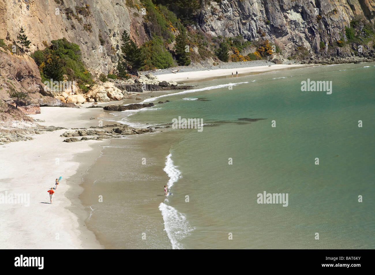 Families on Beach by Doctors Point viewed from Mapoutahi Historic Maori Pa Site north of Dunedin South Island New Stock Photo