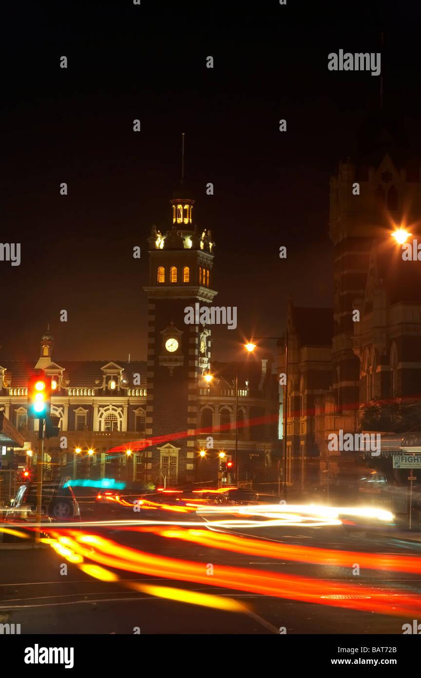 Traffic Lights Tail Lights and Historic Railway Station Stuart Street Dunedin Otago South Island New Zealand - Stock Image