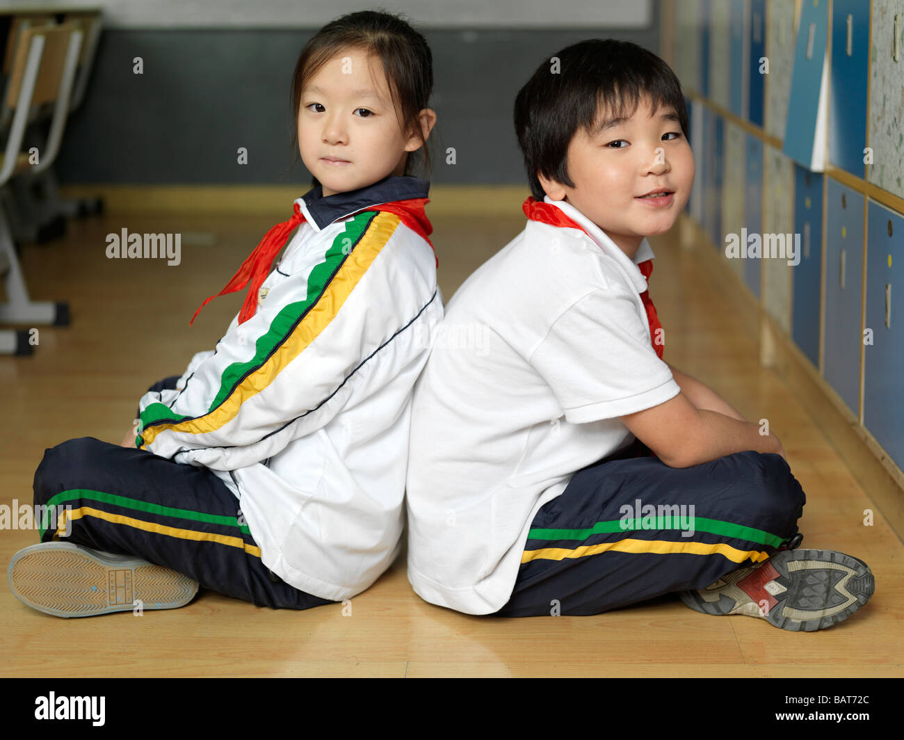 Two classmates sitting Indian-style on the floor of their classroom. - Stock Image