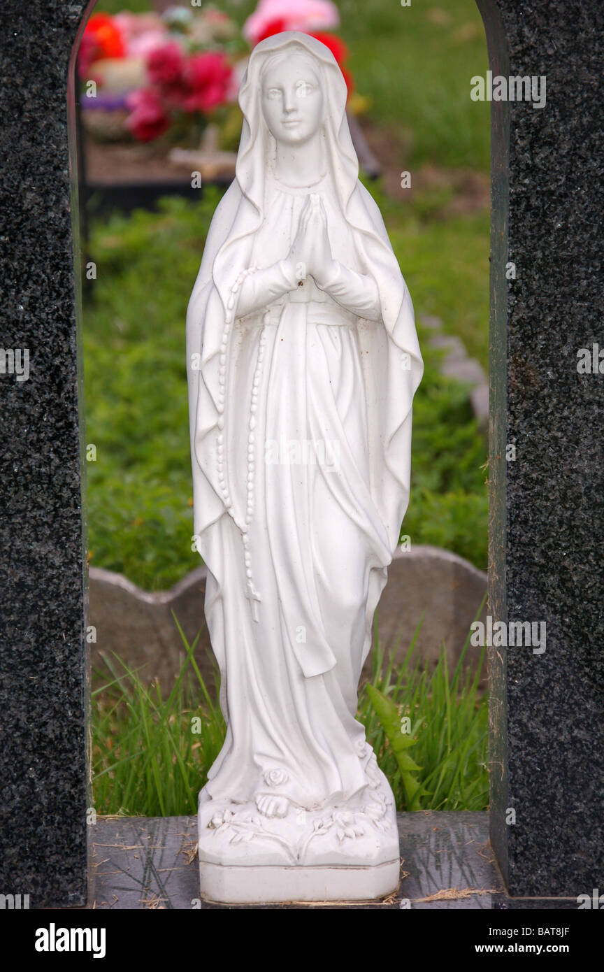 An statue of an angel on a headstone in Roundwood Cemetery, Harlesden, London, England, Uk - Stock Image