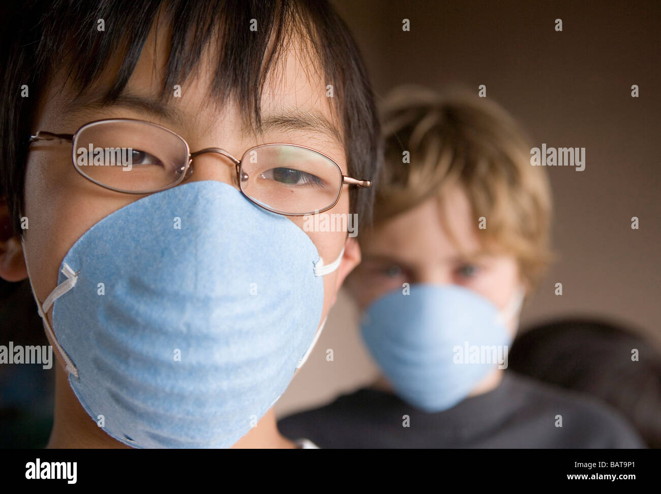 closeup of two children, ages 12 and 10 wearing masks - Stock Image