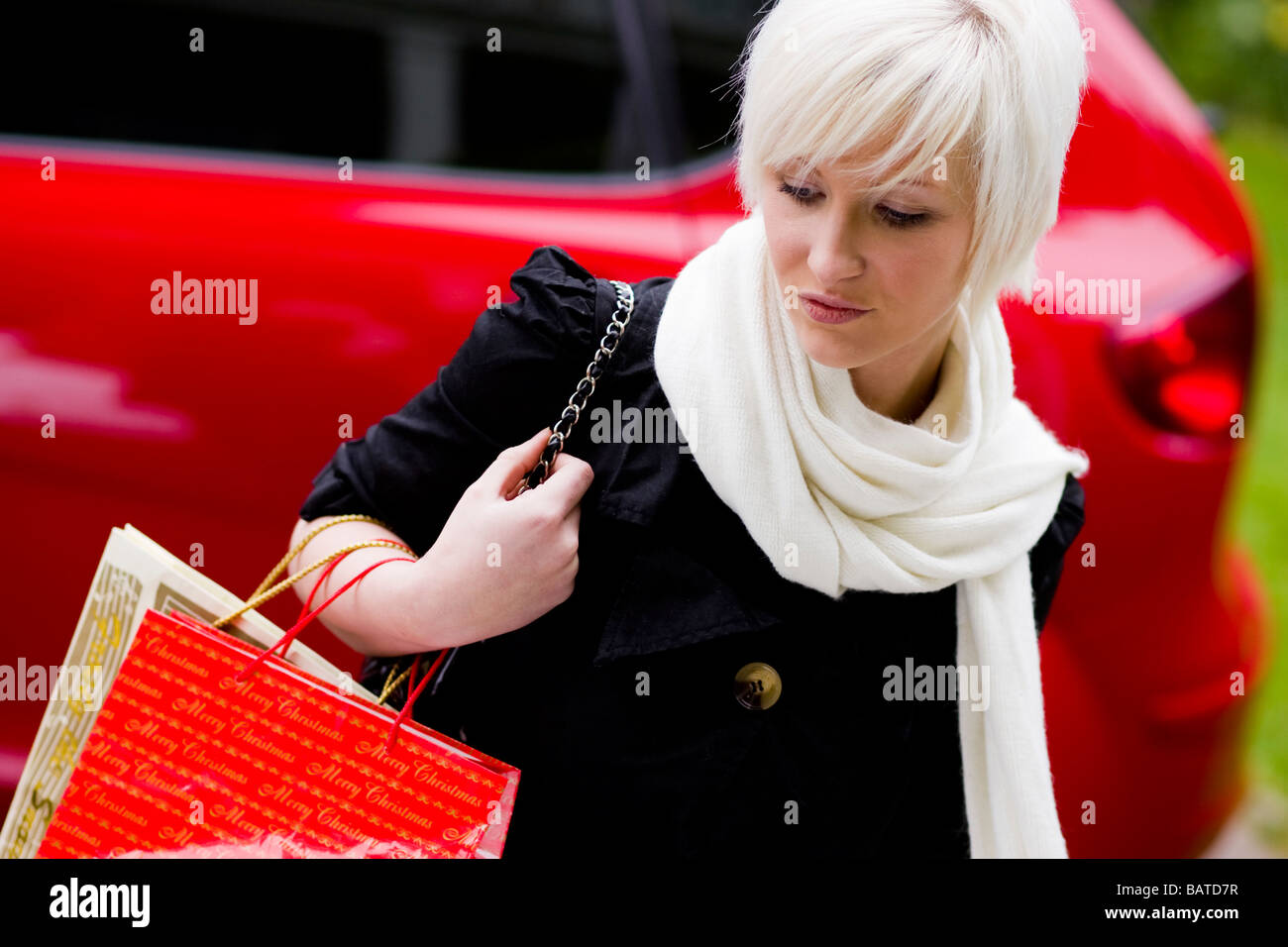 Girl looking depressed with shopping bags - Stock Image