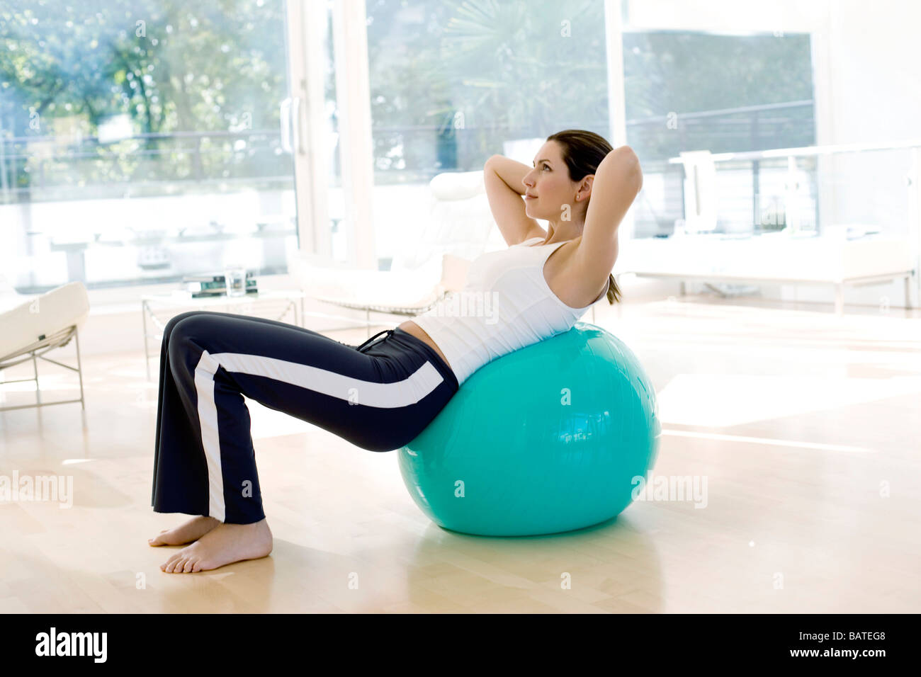 Woman using exercise ball. These balls are used when exercising because their inherent instability. - Stock Image