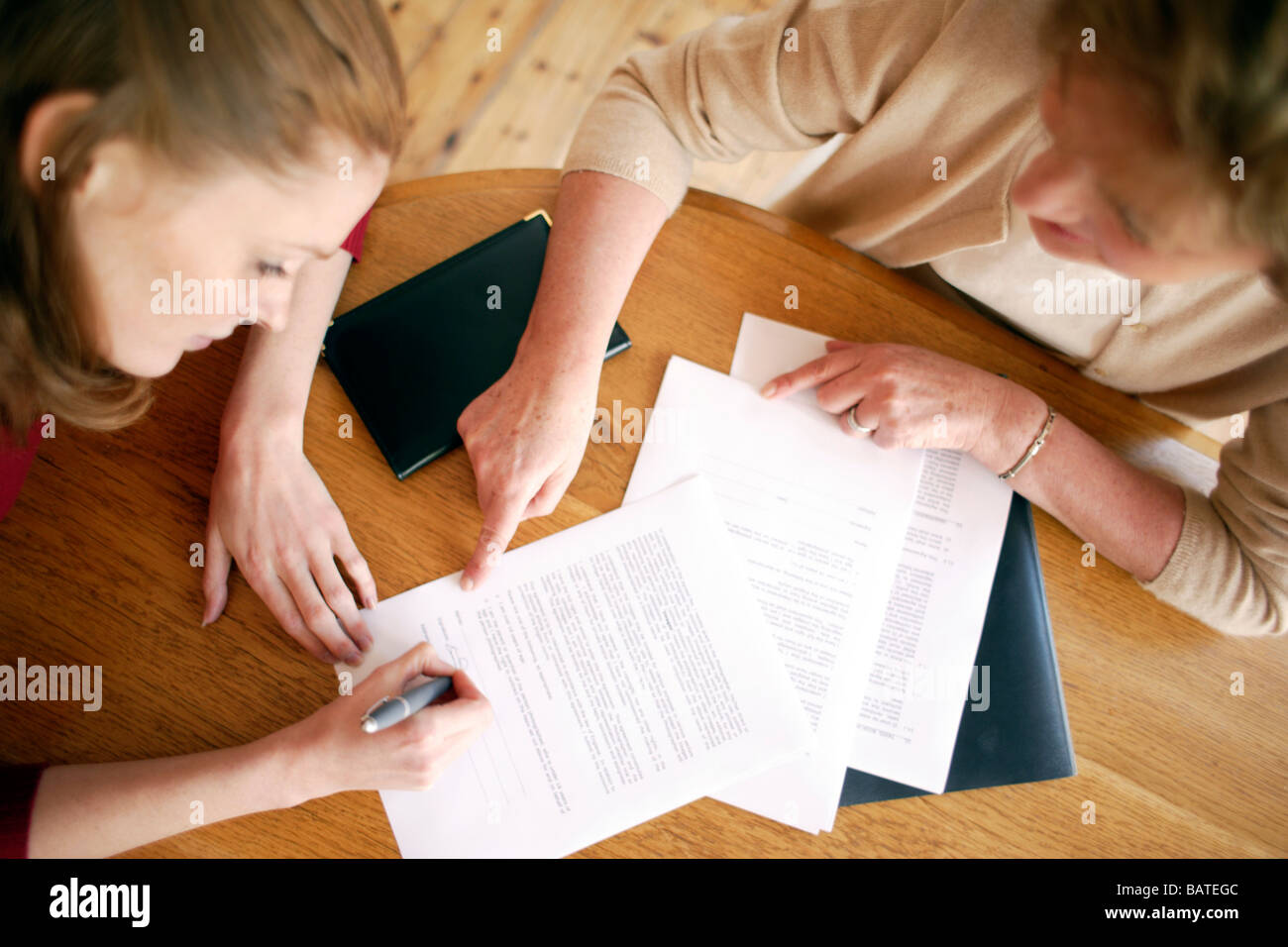 Mother and daughter. Daughter signing forms. - Stock Image