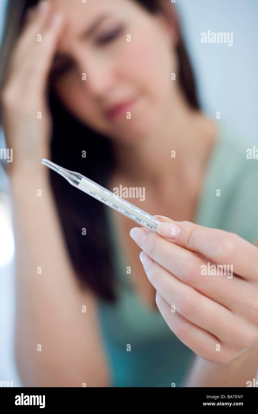Woman using thermometer to diagnose her own body temperature. - Stock Image